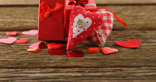 Gift boxes and heart shape confetti on a wooden surface 4k Live Action