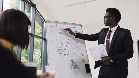 Young businessman conducts presentation using whiteboard on which shows the Footage