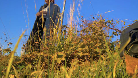 a model in a coat in a park examines dry wild grass in… Stock Video Footage