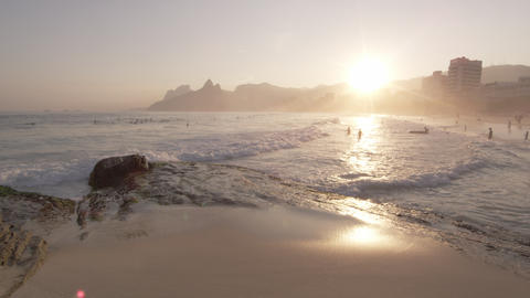 Slow motion, sunset shot of white waves rolling onto beach as people swim Footage
