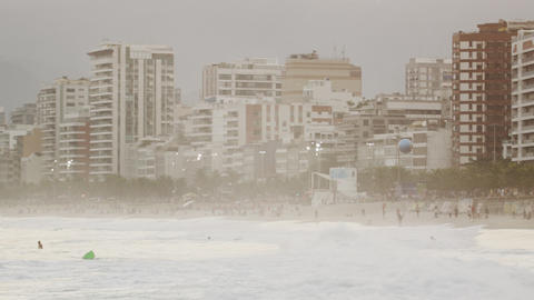 Slow motion, pan shot of beach goers, waves, and buildings in Leblon Footage