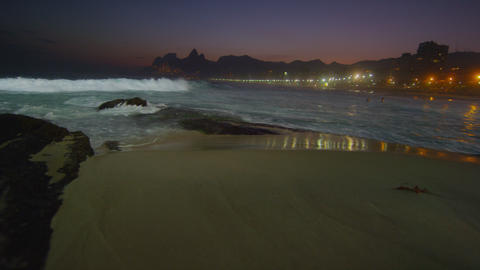 Slow motion, tracking shot of the waves crashing during a night surf at Ipanema  Footage