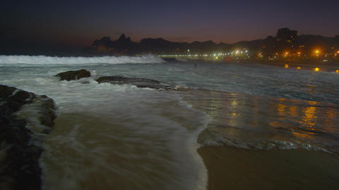Slow motion, pan right of waves crashing against Ipanema beach at night Footage