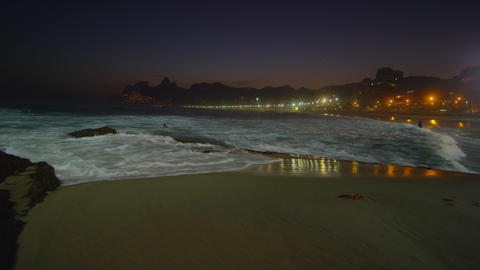 Slow motion, pan left of a night surf on Ipanema beach in Rio De Janeiro Footage