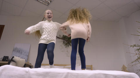 Cheerful girl teenagers having fun in bedroom and jumping on bed i slow motion Live Action