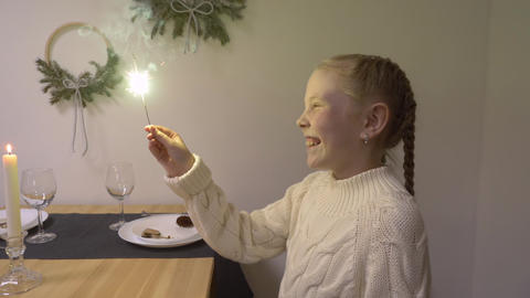 Smiling girl teenager holding in hand bright sparkler sitting at Christmas table Footage
