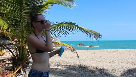 girl uses sunscreen on the beach ビデオ
