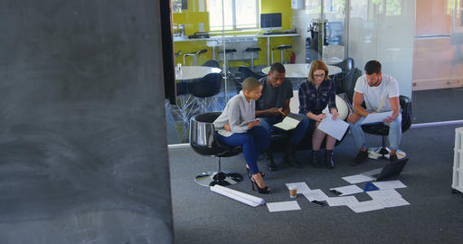 Young mixed race business team discussing over documents in modern office 4k Live Action