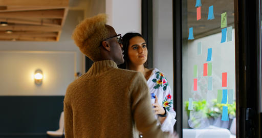 Young mixed race business colleagues discussing over sticky notes in modern office 4k Live Action