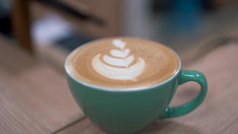 Beatifully prepared hot latte with leaf design in a turquoise cup with perfect Footage