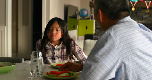 Cute asian granddaughter and old senior grandfather eating food in a comfortable home 4k Live Action