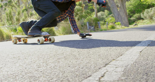 Side view of cool young caucasian man doing skateboard trick on downhill at countryside road 4k Live Action