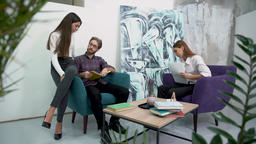 Office workers have a break sitting in comfortable armchairs and talk with each Footage