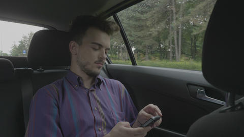 Young entrepreneur man sitting in a back of riding uber cab texting and chatting Footage