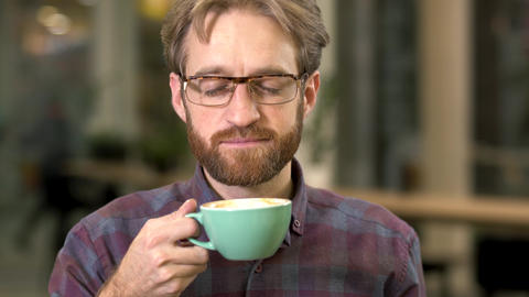 Portrait of a smiling bearded guy in glasses drinking coffee with enjoyment Live Action