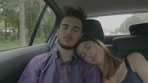 Sleepy young couple taking a nap having the rest in a car on road during the Live Action