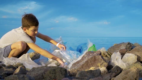 Litle child volunteer cleaning up the beach at the sea. Safe ecology concept Footage