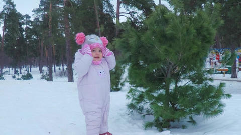 Little girl in the winter forest makes pikabu and smiles Footage