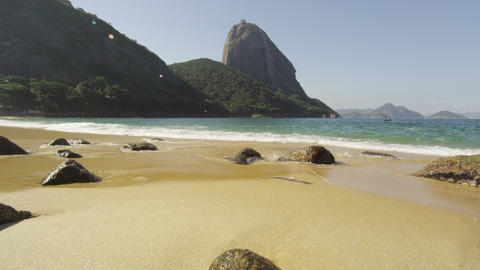 Tracking slow motion shot of Red Beach in Rio with waves washing over exposed bo Footage
