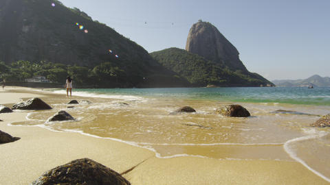 Slow motion shot of a woman walking along Red Beach in Rio Footage