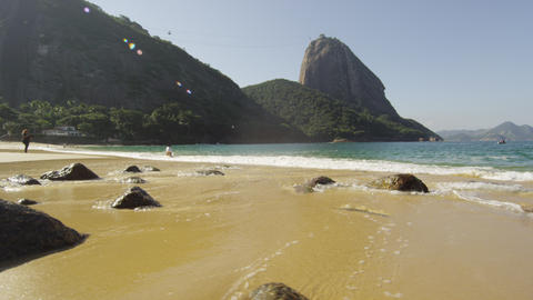 Tracking shot of Red Beach in Rio with waves washing over exposed boulders Footage