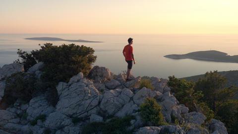 Aerial - Hiker reaching the seaside mountain peak Footage