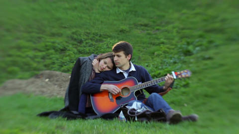 Two young people in love are enjoying the sound of guitar Footage