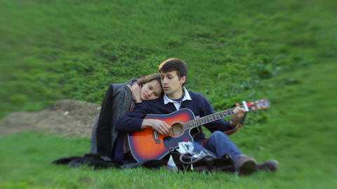 Two young people in love are enjoying the sound of guitar Stock Video Footage