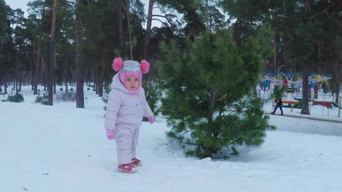 Little girl in the winter forest plays and smiles Footage
