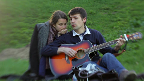 Two people in love are enjoying the sound of guitar Footage