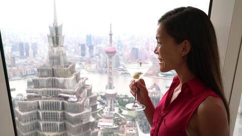 Asian woman drinking martini alcoholic drink while looking at Shanghai view Footage