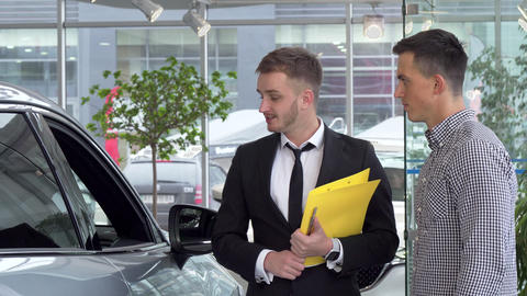 Friendly car dealer helping his male customer choosing automobile to buy Footage