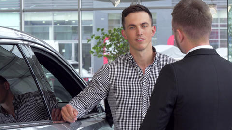 Handsome man shaking hands with car salesman at automobile dealership Live Action