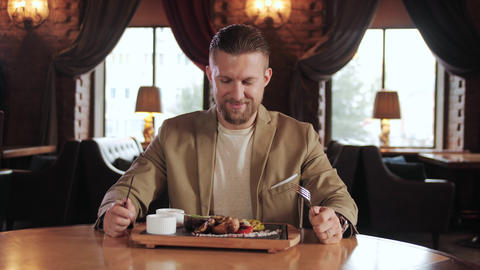 Handsome businessman enjoy a delicacy dinner in luxury grill bar and smile Live Action