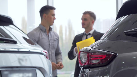 Selective focus on a car, male customer talking to auto dealer on the background ビデオ