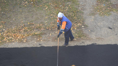 Female worker during asphalting road. Heavy female manual labor in construction Footage