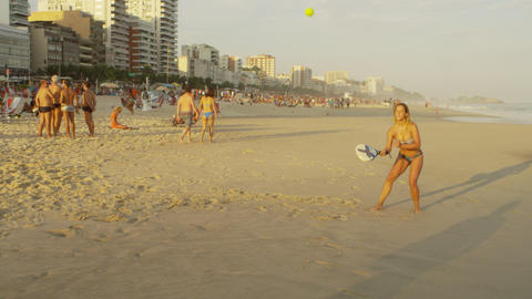 Slow motion footage of a girl playing tennis on Ipanema beach Footage