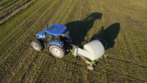 Aerial: Tractor wrapping a bale of hay after collecting the dried hay on a field Footage