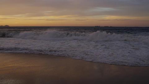 Slow motion, reverse pan shot of waves flowing on to Praia do Diabo (Devil's Bea Footage