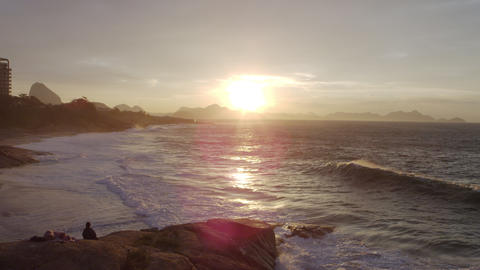Birds fly in from the right across a sunset over the waves at Ipanema Beach Footage