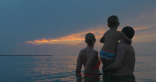Parents and son enjoying evening sky while bathing Footage