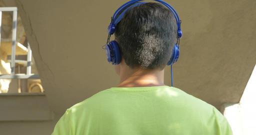Man in headphones walking downstairs Live Action