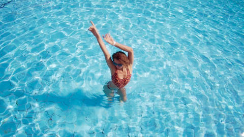 The girl dances in the pool, spreads her hands with water and makes splashes Live Action