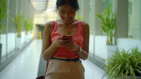 Young woman reading pleasant text on phone enters the building Footage