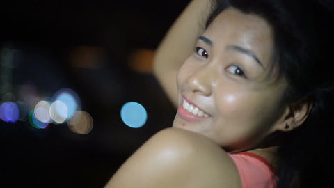 Young Asian woman on a boat and night city on background Footage