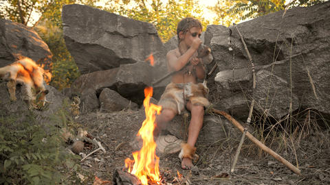 Caveman, manly boy making primitive stone weapon in camp Footage