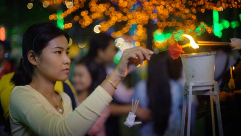 Young Asian woman lighting up candle in order to religious rite ビデオ