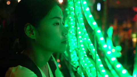 Young Thai girl standing near green light strings Footage