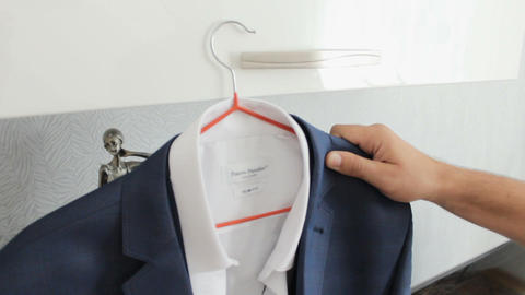 White shirt and blue suit hanging on the hanger. Morning groom Footage