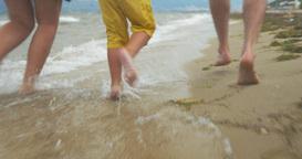 Family of three having fun running on the beach Footage